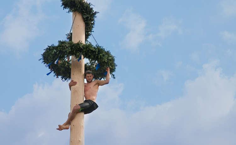 Ein kräftiger Bursch' kraxelt auf den Maibaum